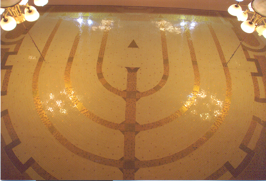 "One of the oldest symbols of the Jewish faith is the menorah, a seven-branched candelabrum used in the Temple. It has been said that the menorah is a symbol of the nation of Israel and the mission to be ""a light unto the nations."" The menorah in the First and Second Temples had seven branches. After the Temples were destroyed, a tradition developed not to duplicate anything from the Temple and therefore menorah's no longer had seven branches. The use of six-branched menoras became popular, but, in modern times, some rabbis have gone back to the seven-branched menoras, arguing that they are not the same as those used in the Temple because today's are electrified. The nine-branched menorah used on Chanukah. Chanukah, the Jewish festival of rededication, also known as the festival of lights, is an eight day festival. (Jewish Virtual Library). The ceiling of the synagogue in Kiev, Ukraine"