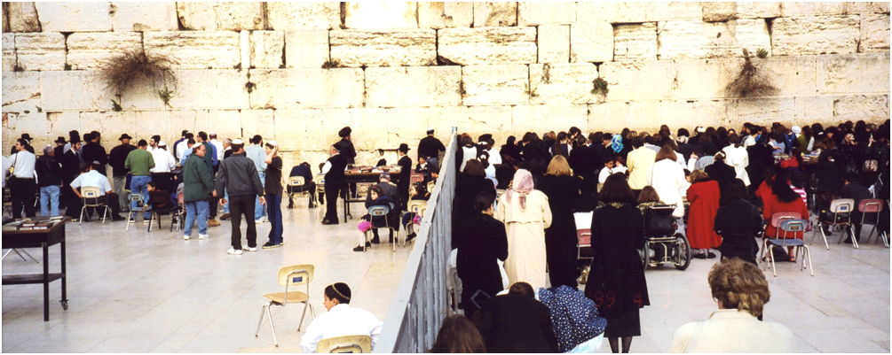 "The Wailing Wall, just below the Temple Mount, Jerusalem. For Jews, this is a place of prayer and pilgrimage. This tradition, dates from the first century CE. This Wall, located in the old section of the city, is the Jews' most holy shrine in Jerusalem. The Wall which is the only part remaining from the Temple, is also known as the Western Wall. Men pray to the left, women and children to the right. Prayers are written on paper and inserted into the cracks of the stone blocks. It is said ""The Sacred Being will never desert the Wailing Wall"". Jews who visit the Wailing Wall mourn the destruction of the Temple and pray for its restoration."