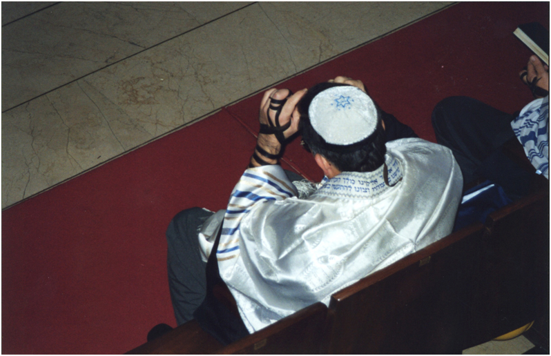 At the synagogue during weekday morning service, a Jew is attaching his tephillin, a box which contains passages from the Torah, to his forehead. There are writings in Hebrew on the collar of his tallith.