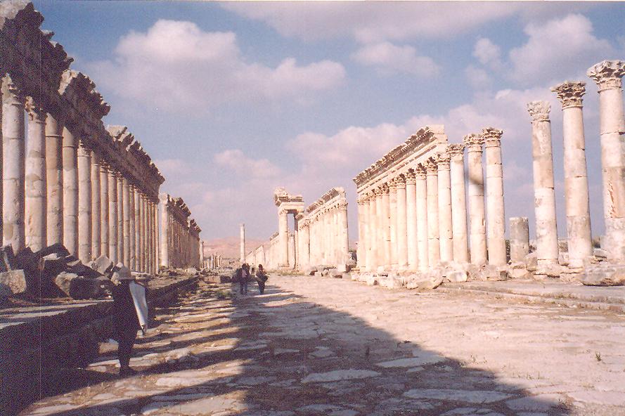Apamea- Şehri, MÖ 3. yüzyılda I. Selevkos kurmuş ve şehre bir Pers olan karısının adını vermiş. Buranın liman şehrini de kurunca oraya da annesinin adını vermiş: Laodicea, günümüzde Lazkiye. Bölge, atları ile meşhur, önemli bir ticaret merkeziymiş. Şimdi, bölgenin en büyük şarap merkezi. Apamea MÖ 1. Yüzyılda Roma'nın eline geçmiş. MS 2. Yüzyılda deprem olunca şehir yeniden inşa edilmiş. Biz, günümüzde bu dönemin yeniden yapımını görüyoruz. Kleopatra ve Marcus Antonius Apamea'yı bizden önce gezmişler. Şehir, Bizans ve iki kez de Pers saldırısına uğramış. 7. yüzyılda Müslümanlar şehri ele geçirmiş. 12. yüzyılda Haçlılar şehri zaptetmiş. Şehir 43 yıl sonra Nurettin Zengi tarafından Haçlılardan geri alınmış. Apamea, pek çok savaş görmüş, üç de büyük deprem geçirmiş: MS 2., 6. ve 12. yüzyıllarda. Apamea'nın ana caddesi (cardo) 2km. Palmira'nın ana caddesinden ve Şam'daki Via Recta'dan daha uzun. İlerde ortada gözüken tek sütun, kavşağı işaret etmek için dikilmiş.