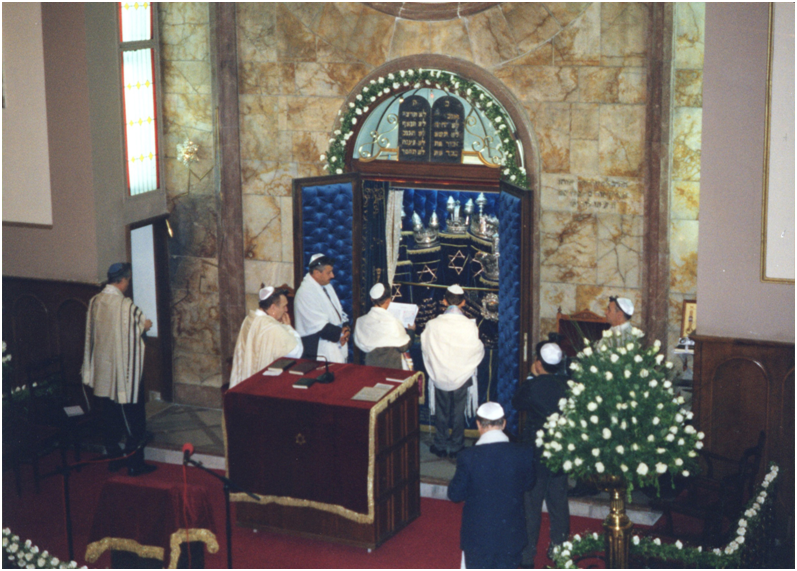 The Ark of the Covenant is opened in front of the Bar Mitzvah twins and they present the Scrolls to the congregation after the reading.