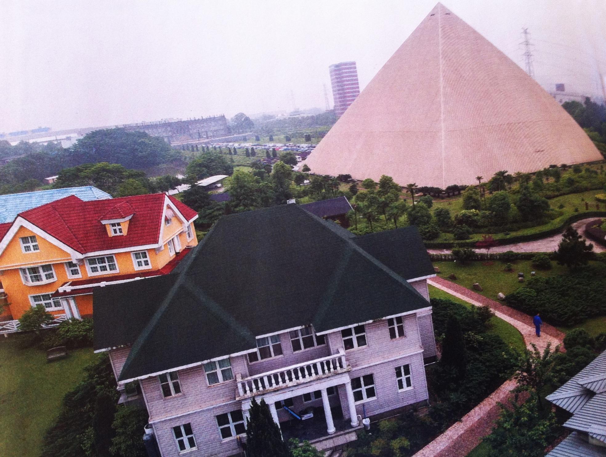 Çin'i 1997 yılında gezmiştim. O zamanlar böyle bir yapılaşma görmemiştim. Geçen ay Bloomberg Businessweek'te, fotoğrafları görünce hem çok şaşırdım, hem çok üzüldüm. Burada sadece birini paylaşıyorum. Diğerleri şunlardı: Hangzhou'da, Paris'teki apartman bloklarının aynısını inşa edip, ortasına bir de Eyfel Kulesi dikmişler !! Şanghay'da Hollanda teması kullanılmış. Çok büyük ebatta tahta ayakkabı, Hollanda tipi evler yapılıp, yel değirmeni de unutulmamış!! Changsha'da, bir havalandırma firması kurduğu kampüste yukarıda gördüğünüz Giza piramidinin replikasını yapmakla kalmamış, kampüsünün ana binasını  Versay ve Buckingham Sarayı'nın parçalarını birleştirerek oluşturmuş, bu binanın önüne de Deng Xiaoping'in heykelini dikmiş. Huizhou'da ise Avusturya modası hakim. UNESCO'nun Dünya Mirası Listesi'ne aldığı Hallstatt evlerinin aynısını yapmışlar!! Tianjin'de, 16. Yüzyılda yaşamış olan Michel de Montaigne'in şatosu inşa edilmiş, ama yeterli gelmemiş olacak ki, önüne bir de Louvre'un cam piramidi eklenmiş.!! Ayrıca Beijing yakınlarında iki harika daha yapılmış: bir Fransız şatosu taklidinin önüne, Roma'daki St. Peter Meydanı oturtulmuş. Bir başka yerde gondola binmek ve ortası havuzlu bir Colosseum izlemek mümkün hale gelmiş. Ülkeyi bu sahte harikalarla doldurmalarını sebebini ise modern ve medeni kent ortamı yaratma gayreti ile açıklıyorlarmış. Tam dosyamıza uygun bir durum.