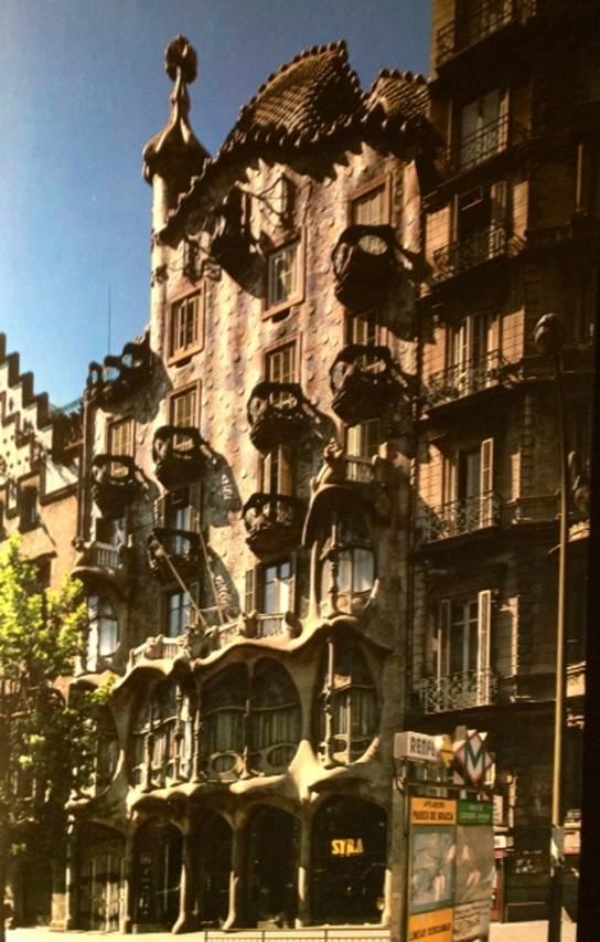 Batllo Evi. Yapım tarihi 1904-1906. Apartmanın yol ile birleştiği yerlere fil ayağı şeklinde inen sütunları, dinazoru andıran çatısı, kuş yuvasına benzeyen küçük balkonları, balık pullarını andıran cephe süslemeleri ile kendini hemen belli eden binanın içi de aynı kıvrımları taşımakta imiş. İki alışılagelmiş bina arasında yer alan ve kendini hemen belli eden bu binanın cephesindeki dalgalanma deniz yüzeyini anımsatmaktadır. O dönemde Barcelona'da merkezi ısıtma olmaması, odaların ayrı ayrı ısıtılmasının gerekmesi Gaudi'ye çok sevdiği bol miktarda baca yapma imkanı vermekte, o da her biri için ayrı ayrı tasarımlar yapmakta idi. Aslında hem bu apartman hem de Gaudi'nin diğer binaları büyük bir heykel gibidir.