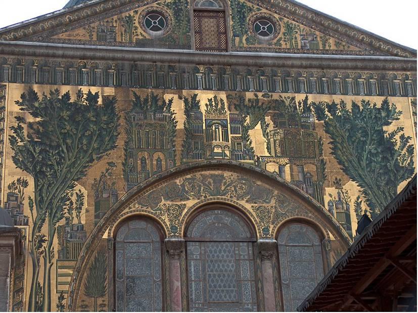Suriye'nin başkenti Şam'daki Emevi Camii'nin giriş kapısı üzerindeki Şam şehrini tasvir eden mozaik panosu, roket isabet etmeden önceki hali ile. Kullanılan tessera seramik değil cam ve taştır. Mozaik kullanımı gibi caminin iki katlı revakları da Bizans'tan alınma. Devşirme mabedi yapan Antakyalı mimarlar daha önce hep kilise yapmışlardı. Caminin planı da bazilikal plandır. Hazine Odası'nın üstünde ve Batı cephesinde de mozaik işlemeler vardır. Batı cephesinde 37 metre uzunluğundaki mozaik tabloda Hz. Muhammed'in Şam'ı seyrettiği söylenen Barada Vadisi tasvir edilmiştir. Cami, 634 yılında, Şam'ın Araplar tarafından alınmasından sonra, Roma İmparatoru I. Konstantin zamanından beri Vaftizci Yahya'ya adanmış Hıristiyan bazilikanın yerine yapılmıştır.