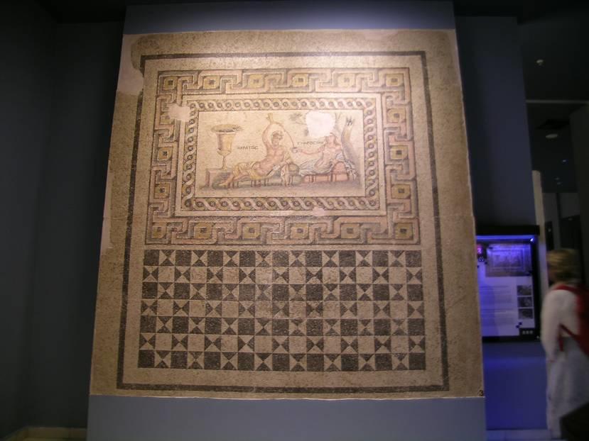 Akratos mozaiği, Mainad Villası'nın muhtemelen dinlenme odasının taban mozaiği olup 4.00 x 3.50 m. boyutundadır. Mozaiğin üst yarısı figürlü, alt yarısı ise geometrik desenlidir. Figürlü panonun çevresi en dışta üç boyutlu meander ( Menderes Irmağı'nın kıvrımlarından esinlenen, anahtar motifi de denilen, Antik Çağ'da çok yaygın olarak kullanılan şerit ) motifi ve onun içinde ikili saç örgüsü motifi ile çevrilidir. Figürlü panoda üç güzel kız kardeşten biri olan Euphrosine ve Akratos divanlara uzanmışlardır. Güzellik, neşe ve mutluluğun hakim olduğu bir sahnedir. Euphrosine sakinliği, kendine güveni, serinkanlılığı, erdemliliği ve tedbiri simgelerken Akratos zayıf erkek karakterini temsil eder.  Bu mozaik taban MS 2. yüzyıl sonları ile 3. yüzyıl başlarına tarihlenmektedir.