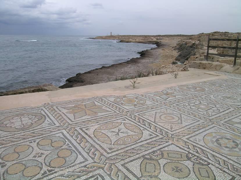 """2005 yılında Libya'da gezerken en yadırgadığım şeylerden biri, bazı yerlerde dünya kültür mirasının üzerine basarak gezmekti. Bazı yerlerde hiçbir koruma yoktu. Mozayiğin orjinal yerinde (in situ) sergilenmesi hedeflenebilir, hatta tercih edilebilir. Ancak fotoğrafta görüldüğü gibi denizin olumsuz etkilerine bu kadar açık konumda olmasına ve biz turistler Sabratha'nın tiyatrosuna giderken üzerinden yürümemize rağmen yüzlerce yıllık mozaik döşemenin ne kadar iyi durumda olduğunu görüyorsunuz.Tabii """"Bahar"""" olaylarından sonra geriye ne kaldı, o da ayrı bir şey."""