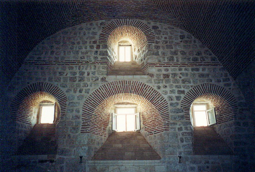 Mor Gabriel Manastırı, Anastasya Kilisesi. Manastır pek çok defa yağmalandığı için açıklıkları küçük tutmak daha güvenli bulunmuş. Bölgede hakim olan karasal iklim de bir başka nedendir. Mimarlar dışarıdan küçük ancak içeriye doğru genişleyen 'abajur pencereler' yapmışlardır. Pencerelerin eğik denizlikleri, ışığın yansımasını sağlar. Pencere sövelerini abartılı taş bezeme ile kaplamak da sık yapılan bir uygulamadır.