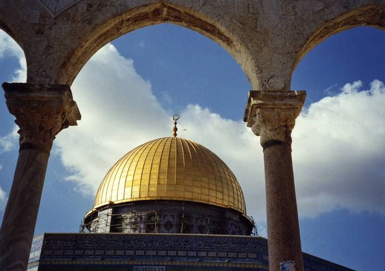 Jerusalem – In the higher part of the Temple Mount stands the Dome of the Rock, with its golden cupola, known also as the Mosque of Omar. It was built in the seventh century. Inside, is the Rock which is sacred to Jews and Muslims alike. It is sacred to the Jews because they believe that the episode of Abraham and Isaac took place there. For the Muslims, from which Mohammed rose to Heaven during his dream-visit. The Rock is marked with Mohammed's footprint.