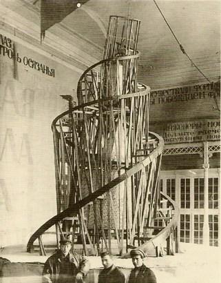 """Vladimir Tatlin, Üçüncü Enternasyonel'e ait Anıt'ın modeli, 1919. Modern Müze, Stockholm, İsveç. Bu abartılı sentez, resim, heykel ve mimarlığın devletin propaganda ve enformasyon organıyla birleştiğini gösteren en iyi simgedir. Bu yapı için tasarlanan yükseklik en az Empire State binası kadar olacaktı, yani en az 375m. İçinde toplantı salonları, bürolar, en tepede de enformasyon merkezini barındıran bir silindir, bir küp ve bir kare yer alacaktı, tümü ayrı hızda dönecekti. Bu tasarım, kinetik mimarlığın ilk örneklerinden biridir. Özel bir projeksiyon aygıtı ile halka her gün, her saat yeni bültenler, hükümet bildirileri ve devrimci sloganlar verilecekti. Kule, SSCB'nin pek çok kentinde sergilendi, gezdirildi, üzerinde kule resmi olan pul hazırlandı, büyük heyecan yarattı. """"Dünya işçileri arasındaki uluslararası bağlaşmanın yalın ve yaratıcı bir biçimde en ideal, en canlı ve klasik ifadesi"""" olarak tanımlandı. Anıt model olarak kaldı, hiç gerçekleştirilmedi ama bütün dünyanın ilgi odağı oldu. Fakat çok geçmeden Rus halkı arasında alay konusu oldu."""