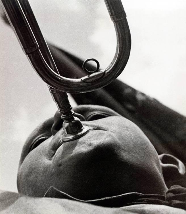 """Aleksandr Mihayloviç Rodçenko (1891- 1956), Rus heykeltıraş, fotoğrafçı ve grafik tasarımcısı, Konstrüktivizm'in kurucularından biridir. Fotomontaj ve fotoğrafçılığa başlamadan önce ressam ve grafik sanatçısı olarak çalıştı. Resimleri sosyal içerikleri olan, yenilikçi ve ressam estetiğine aykırı çalışmalardı. Fotoğraflarını genellikle sıradışı açılardan çekerdi. Uzunca süre fotoğraf filmlerinde taban olarak cam kullanılmıştı. 1870'li yılların ortalarına doğru gümüş bileşiklerinin jelatin taban üzerine kullanımıyla, cam negatiflerde çıkan problemlerin çoğu çözüldü. Rodçenko, jelatin gümüş baskı yöntemini kullandığı, alışılmamış açılar kullanarak çektiği fotoğraflarıyla fotoğrafçılığı """"görüntünün kaydı"""" olmaktan çıkardı. Arkadaşı Mayakovski'nin dergi kapaklarını, Potemkin Zırhlısı'nın afişlerini, 1925 Paris'teki Sovyet pavyonunun tasarımını yaptı. Avrupa'da da ünlü oldu. 1930'larda SSCB'de politik iklim değişti. Yukarıda görülen 'Pioneer with a trumpet' adlı eseri yüzünden formalist olmakla suçlandı. Ekim grubundan ayrılmak zorunda kaldı."""