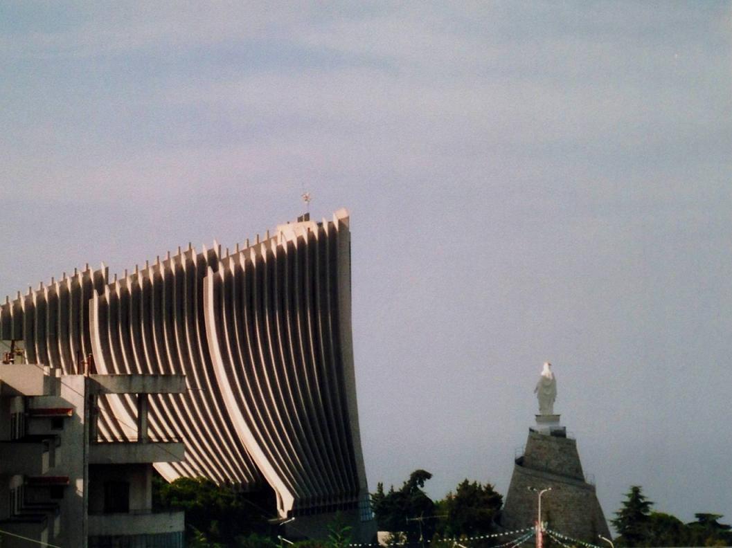 """Lübnan Dağı'nda Harissa. """"Lübnan'ın Bakiresi"""" heykeli ve 1908 yılında inşa edilmiş modernist Maruni Katedrali. Meryemana heykelinin kaidesi, Lübnan'ın sembolü sedir ağacının gövdesinden esinlenerek Fransız mimar Gio tarafından tasarlanmış. Bu heykel Marunilerin sembolü ve Marunilerin en büyük katedrali ile yan yana. Heykel Lyon'da bronzdan yapılıp beyaza boyanmış. Kaidenin altında da mabet var. Mabedin girişinde, """"Lübnan'da bulutlar gibi yükseldim"""" yazılı. Buraya çıkan yol çok virajlı ama manzara çok güzel, Akdeniz, Juniah Körfezi ayaklar altında. Dini festivaller burada yapılıyor; hacı olmak isteyenler kaidesinin etrafında, dönerek yükselen merdivenleri çıkıyorlar."""