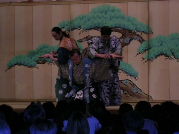 """19 Nisan 2006 tarihinde sahnede izlediğimiz Kyogen Ancient Comic Play'den bir enstantane. Noh'da lüks kostümlü maskeli aktörler vardır ve Noh'un perdeleri arasındaki komik ara piyesi olan Kyogen ile birlikte sunulur; bunların her ikisi de UNESCO tarafından """"başyapıt"""" olarak tanımlanmıştır."""