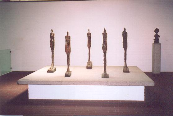 Alberto Giacometti, çağlar boyunca insan imgesini dile getirirken kullandığı ince uzun figürleri, yarınlarından emin olamayan insanların hem güçsüzlüğünü, hem de dayanıklılığını mükemmel bir biçimde ifade ederler.  Helsingor, Louisiana Açık Hava Müzesi, Danimarka.