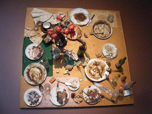 1930 Romanya doğumlu, İsviçreli sanatçı  Daniel Spoerri yapıtlarında rastlantı ve geçicilik temalarını kullanmıştır. Tuzak tablolarında çeşitli ögeleri bir yüzey üzerine tespit etmiş; kullanılmış, eskimiş nesneleri sanat eserinde tekrar kullanmıştır. Tuzak tablolar (trap pictures), o anı çerçeveler. Böylelikle, bu nesneler, yeniden bir gerçeğin belirtgesi olmuştur. Afişler, yemek artıkları, tabak, çatal, bıçak gibi eşyaları eserlerinde kullanmıştır. Spoerri, Yeni Gerçekçilik akımının yanı sıra Fluxus ve Eat Art ile de ilişkilendirilir. Restaurant de la City Galerie, Daniel Spoerri, 1965. Fotoğraf:www.flickr.com