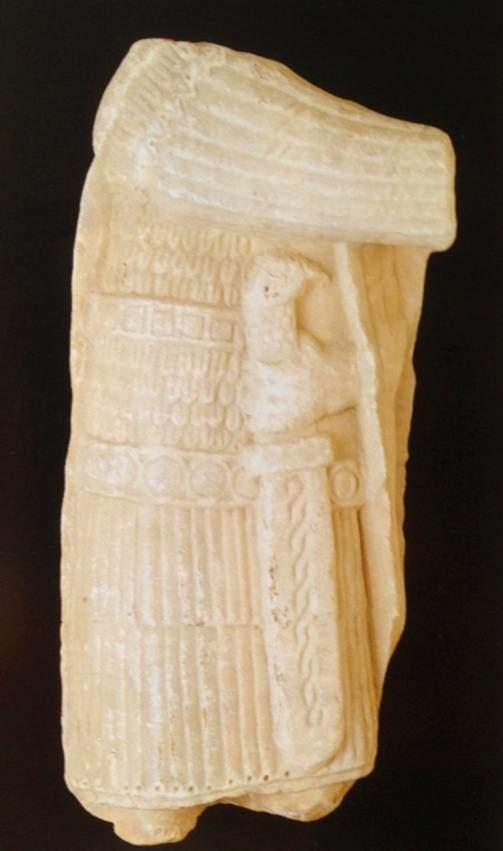 İstanbul Arkeoloji Müzeleri'nde sergilenmekte olan bu mermer heykel parçasında askeri bir kostüm örneği görüyoruz. Diz üzerine kadar gelen tuniğin kolları uzun. Göğüs kısmı metalli, etek kısmı ise deri şeritli. Omuza bir harmani atılmış, sol elde kabzası akbaba kafası ile süslü kısa ve geniş bir kılıç var.