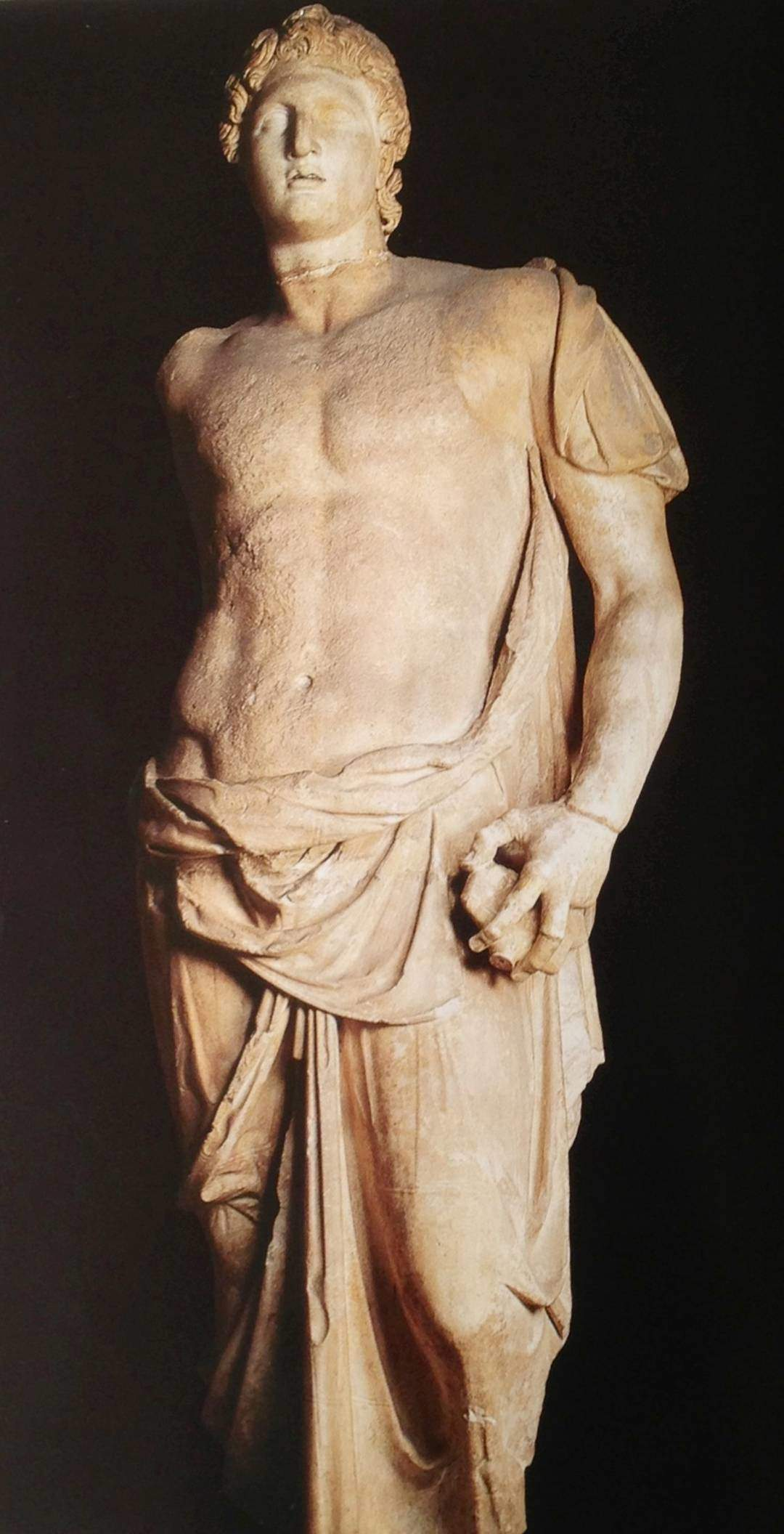 """Büyük İskender. Manisa'da bulunmuş bu mermer heykel MÖ 3. yüzyıl ortasına tarihleniyor. Yüksekliği 190 cm. Heykel en iyi kalite beyaz mermerden yapılmış. Başı ise farklı bir bloktan işlenmiş. Baş kısmında bir sıra halinde yer alan çukurlar, yapıldığında metal bir tacı olduğunu gösteriyor. Sol eliyle bir kılıcın kabzasını tuttuğu görülürken, sağ elinde bronz bir mızrak tuttuğu düşünülüyor. Bu silahlar olmasa, kolaylıkla bir Apollo heykeli olabilir. Hülyalı bakış, hafif aralık dudaklar Helenistik dönemde ve Pergamon heykel sanatında tanrıların, özellikle de Apollo'nun tipik  betimleniş şeklidir. Dünyadaki pek çok müzede yer alan Büyük İskender heykellerinden farkı imzalı olması. Sanatçı, """"Aias'ın oğlu, Pergamonlu Menas'ın eseridir"""" diye yazmış. İstanbul Arkeoloji Müzeleri."""