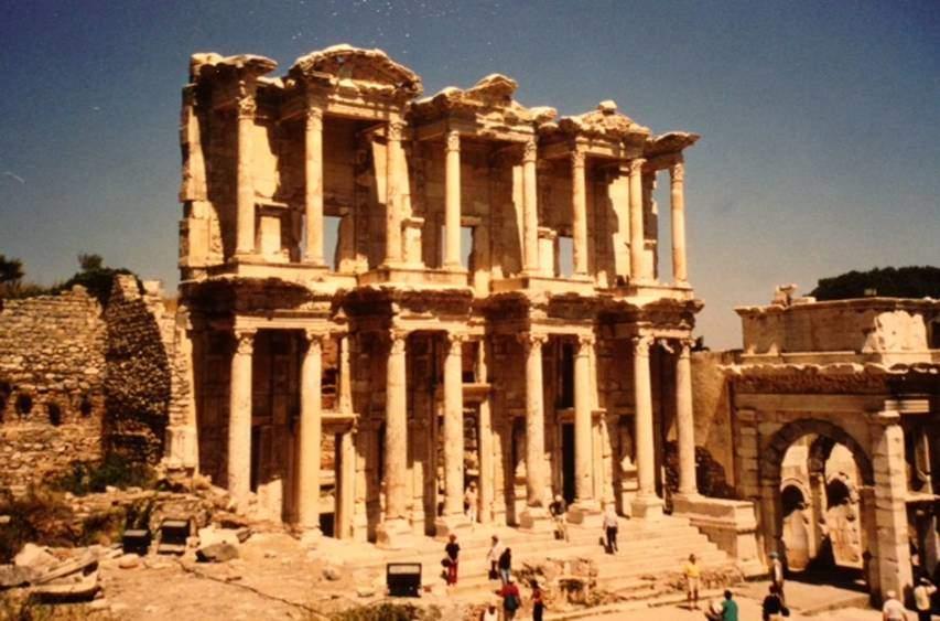 MS 2. yüzyıla tarihlenen Celsus Kütüphanesi'nin cephesi. Fasadın sağında Agora'nın Güney Kapısı, solunda Helenistik döneme ait peristilli ev (peristil: sütunlarla çevrili, bahçe gibi avlusu olan ev veya ön yüzünde sütunlu girişi olan ev). Kütüphane yapılırken evin bir kısmını yıkmışlardı. Ephesos'taki Celsus Kütüphanesi'nin ön cephesi 1905-6 yılında ortaya çıkarılmış, 1970-1978 yıllarında yeniden ayağa kaldırılmıştır. Roma Çağı'nın tipik özelliklerinden biri kütüphane cephelerinin çok süslü oluşlarıydı. Nişler, alınlıklar ve sütunlar gibi girintili çıkıntılı mimari ögelerden oluşan cephe düzenlemesi, tamamen Romalı bir anlayıştır. Helenistik ve Roma mimarisi arasındaki fark, Helenistik Dönem yapı ön yüzlerinde egemen olan yatay düzenlemeye karşın, Roma Çağı cephelerinde dikeyliğe önem verilmesidir. Fotoğraf, 2001 yılında çekilmiştir.