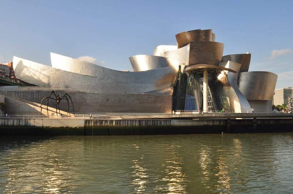 Guggenheim Müzesi, Bilbao, İspanya. Yapısökümcü mimarinin belki de en ünlü örneği fantastik ve ileri teknoloji ürünü olan bu müzedir. 1997 yılında açılan müze, Kanadalı-ABD'li mimar Frank Gehry'nin tasarımıdır. Binanın cam ve titanyum konturları bir gemiyi hatırlatır. Bir liman kentinde yapılmış olan müzenin yansıtma panelleri balık pullarını akla getirir. Oyunbaz ve fantastik bu mimari yaklaşım İspanyol (Bask) mimar Antoni Gaudi'ye (1852-1926) kadar geri götürülebilir. Gehry, Yapısökümcü etiketini reddeder. Fotoğraf:openbuildings.com