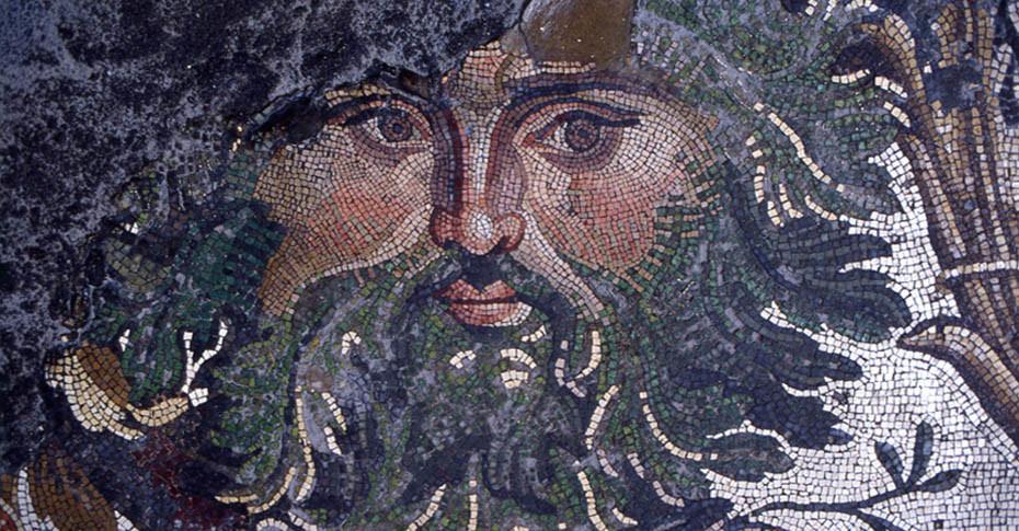 """Bizans İmparatoru Konstantin ( 306-337), 324 yılında Konstantinopolis adını verdiği """"İkinci Roma""""yı kurar. Şehrin saray bölgesinin 532 yılında meydana gelen Nika Ayaklanması sırasında önemli ölçüde yakılıp yıkılmasından sonra İmparator I. Justinyen (527-565), saray yapılarının köklü onarımını ve yenilenmesini sağlar. Bu dönemde inşa edilen sütunlu, revaklı salonlara çok renkli mozaik tabanlar döşenir. İstanbul Büyük Saray Mozaiğinin döşenme tarihi 6. yüzyılın ilk yarısıdır. Kurtarma işlemi 1983-1987 yılları arasında Türk-Avusturya işbirliği ile tamamlanmış, sonra onarım ve koruma işlemleri başlatılmıştır. Parçalar, 1987 yılında kurulan Büyük Saray Mozaiği Müzesi'nde sergilenmeye başlanmıştır. Yüzey alanı 1872 metre kareyi bulan Büyük Saray Mozaiğinin üstün sanat düzeyi nedeniyle Geç Antik Çağ'dan bilinen hiç bir renkli taban döşemesi ile mukayese edilemeyecek bir şaheser olduğu düşünülmektedir. Bir metre karelik alana ortalama 40.000 tessera kullanılmıştır. Yapıtın ancak 1/7 veya 1/8'lik bölümüne erişilebilmiş olmasına rağmen çağının mozaik sanatının olağanüstü yoğunluktaki resim kompozisyonlarından biridir. Elimizde eserin 180 metre karelik bütünlüğü zedelenmemiş bir parçası bulunmaktadır. Mozaiğin düzenlenişinde Bizans imparator saraylarında da, Helenistik-Roma döneminden kalma, mekan içi duvarlar, döşemeler, tavanlar gibi geniş alanların anıtsal manzara resimleriyle bezenmesi geleneğinin devam ettiği görülmektedir. İstanbul Büyük Saray Mozaiği. Akantus sakallı mask. Güneybatı salonu duvarına bakan yüzden. Fotoğraf: www.ayasofyamuzesi.gov.tr"""