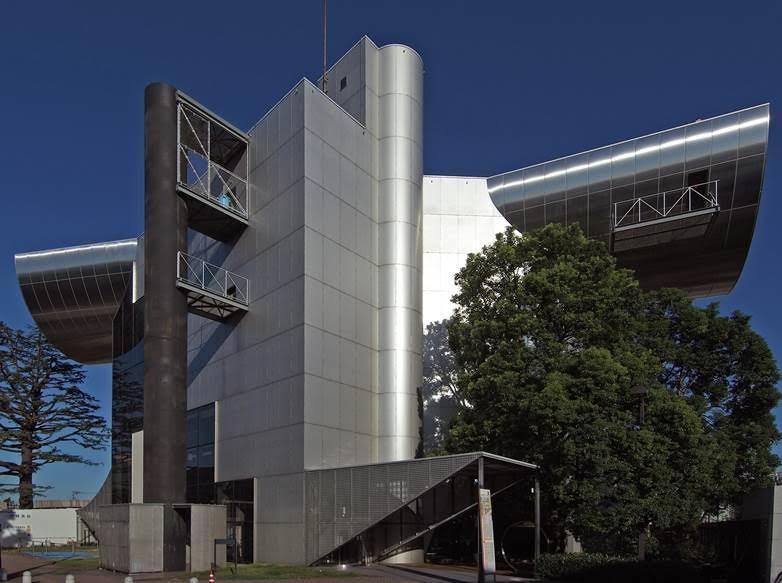 """Charles Jencks'e (1939) göre ise Yeni Modern'i en iyi tanımlayan mimar Japon Kazuo Shinohara'dır (1925-2006). Tokyo Teknoloji Enstitüsü için tasarladığı, 1987 yılında açılışı yapılan bina uçan makinaları anımsatacak biçimdedir. En tepedeki yarım çelik silindir, 747'nin kanadı gibi havada asılı durur. Bu, dalgalanan geometrik formun bir örneğidir. Shinohara, 1988 yılında yayımladığı Kaos ve Makina adlı metninde Modern Next- Modern Ardı tanımlamasını yapar. Tokyo bugün biçimler, renkler ve malzeme itibarıyla görsel çevre anlamında dünyanın en kaotik kentlerinden biridir. Shinohara, geometri-rastlantı ve gürültü- düzen ve kaos karışımını gelişmeci anarşi olarak yorumlar. Modernist teknoloji ve makinaya verdiği ağırlık onu amacına, Modern Ardı'na götürür. Görsel olarak sonuç Frank Gehry ve Dekonstrüktivistlerin çalışmalarına yakındır. 2010 yılındaki Venedik Bienali'nde anısına Altın Arslan ödülü verilmiştir. Fotoğraf:Tokyo Institute of Technology Centennial Hall 2009"""" by Wiiii - Own work. Licensed under CC BY-SA 3.0 via Wikimedia Commons."""