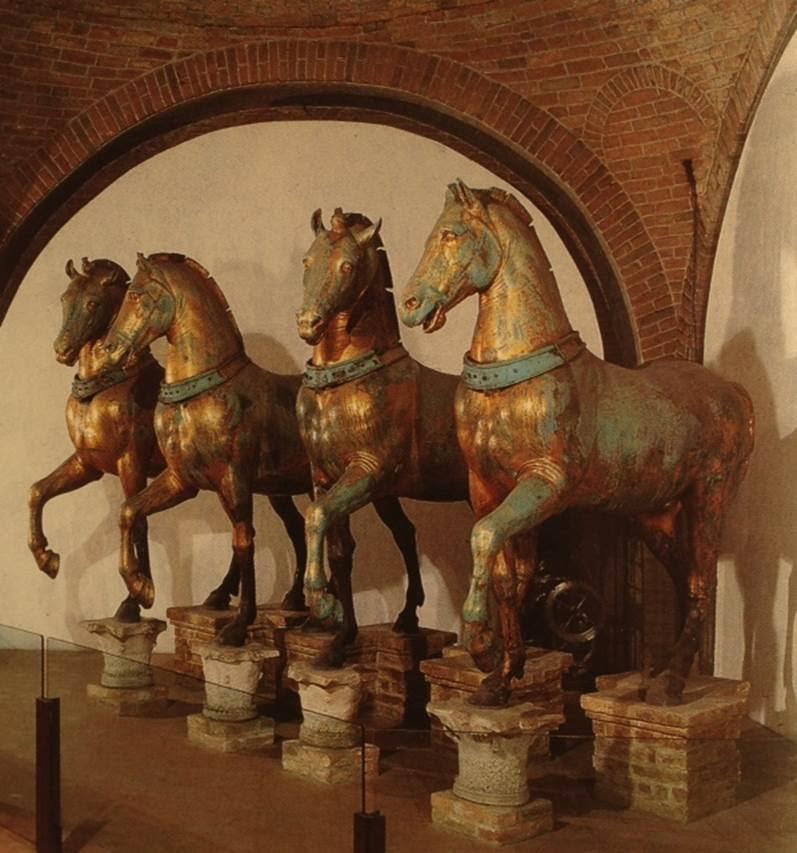 Roma İmparatorluğu Doğu-Batı olarak ikiye bölündüğünde Venedik Doğu Roma sınırları içinde kalmıştı. Konstantinopolis'in Latin işgali ile kaybettiği hazinelerden biri güç, egemenlik ve zafer alaylarının sembolü olan Quadriga, dört at anıtı, Venedik'e götürülmüştü. Bu ganimetin, taşıdığı sembolik anlamdan ötürü, Bizans'ın onurunu kırmak gibi bir siyasi misyonu da olmuştur. Quadriga Konstantinopolis'te muhtemelen bir zafer takı üzerinde Hipodrom 'da yer alıyordu. Napolyon, Quadriga'yı 1797'de Paris'e götürmüş, Quadriga 1815 yılında tekrar Venedik'e dönmüştür. Dünya Savaşları sırasında korumaya alınan Quadriga, hava şartlarının neden olduğu tahribattan etkilenmesini önlemek için kaldırılmış ve 1980 yılında replikası yapılmıştır. Fotoğrafta görülen altın kaplama orijinal Bizans atları müzede korunurken, replikaları San Marco Bazilikasının ön cephesinde, iki katlı kemerlerin arasındaki terasta sergileniyor. Atlardan ikisinin replikası Stockholm'de ve Kopenhag'da bulunuyor. Sanatçı Handan Börüteçene'nin gerekli izinler alınarak, orijinal atların mulajı çıkartılıp, Sultanahmet Meydanı'na, orijinal yerlerine konmasını sağlamak için geliştirdiği proje ne yazık ki hayata geçirilemedi. Oysa, pek çok şehirde quadriga heykelleri olmasına rağmen, günümüze ulaşmış tek antik quadriga şehrimize aittir. Hüseyin Alptekin, 2005 İstanbul Bienali'ne bu atların kopyalarını getirip sergilemişti. Fotoğraf: Venice, Stefano Zuffi, Leonardo Arte, 1999.