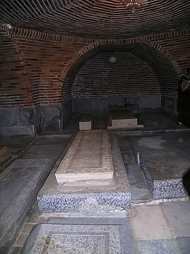 """Kripto. Gur Emir'de lahitlerin bulunduğu mozole salonu altın yaldızlı, nakışlı, çinili. Alt kattaki asıl kabir odası ise basık tavanlı, rutubetli bir yer ve tek bir çıplak ampulle aydınlatılıyor. Fotoğrafın merkezindeki Timur'un mezarıdır. Sovyet antropolog Mihail Gerasimov 1941 yılında Timur'un kabrini açmaya geldiğinde bir yazıtla karşılaşmış. Yazıtta: """"Her kim benim mezarımı açacak olursa benden daha beter bir düşman bulacak"""" deniyormuş. Nitekim ertesi gün Hitler SSCB'ye saldırmış. Fotoğraf: Füsun Kavrakoğlu"""