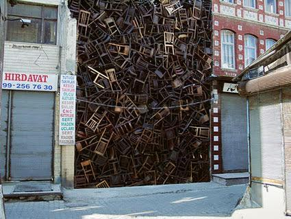 Kolombiyalı sanatçı Doris Salcedo'nun (1958-), 2003 yılında yapılan 8. İstanbul Bienali için yaptığı enstalasyon. Sanatçı, Eminönü'ndeki iki binanın arasına, üç kat yüksekliğinde, 1550 sandalyeyi yığmıştı. Bir yıl önce de aynı işi 280 sandalye ile Bogota'da Adalet Sarayı'nda uygulamıştı. Bogota'daki amacı, burada, on yedi yıl önce hükümeti devirmek için başarısız bir girişimde bulunup ölenleri anmaktı. İstanbul'daki yerleştirmesinin amacı ise, global ekonominin çarklarını çeviren kimliksiz göçmen kitleleri anımsatmak idi. Doris Salcedo, genelde mobilyalarla çalışan bir sanatçı. Bunlarla yaptığı enstalasyonlarında yerleştirmenin içinde bulunduğu alanın tarihiyle, belleğiyle, kültürüyle bütünleşmeyi amaçlar. Fotoğraf:www.universes-in-universe.de