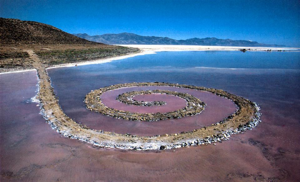 Spiral Jetty (Spiral Dalgakıran), Robert Smithson, 1969-1970. Bu sarmal eser yaklaşık 450 metre uzunluğundadır. Balçık, kaya, tuz kristali ve suyla yapılmıştır. Eser, ABD'nin Utah Eyaleti'nde Büyük Tuz Gölü'nde 4 hektarlık bir alanı kaplamıştır. Alana 6500 tondan fazla malzeme taşınmıştır.  Çalışmada kullanılan alan Utah Eyaleti'nden 20 yıllığına kiralanmıştır. Eser, *sanatsal olmayan malzemeler kullanmıştır; malzemeler hem geleneksel değildir hem de doğaldır, *sanatla ilgili beklentilerin uzağındadır, *bir galeride veya müzede değil, dışarıdadır; müze ve galerinin rolünü sorgular, *bu organik, doğal şekil soyut bir tasarım olarak da görülebilir, *ürün, aynı zamanda sanat yapma süreci hakkındadır, *doğası gereği sürekli değişen bir yapıdır; Smithson'un temalarından biri olan entropi, yani bütün doğal fenomenin aşama aşama yavaşlaması ve son bulmasıdır, *genellikle bir sanat eserinin sonsuza kadar kalmasını bekleriz ama Spiral Jetty 1972 yılında sular altında kalmıştır. Sular çekilince tuz kristalleri kayaların beyazlaşmasına yol açmıştır, *bu Arazi Sanatı örneği, hareket, yer değiştirme ve değişim hakkında olduğu kadar, radikal biçimde değişen bir dünyada sanatın anlamı, sembolizmi ve yeniden tanımlanması hakkındadır. Smithson, doğadaki yaşam-ölüm döngüsünden, yaşamsal entropiden etkilenmiş, başka yapıtlarında da spiral biçimini kullanmıştır. Smithson, Arazi Sanatı örneklerini mekan ve mekan dışı olarak ikiye ayırmıştır. Böylece, arazide gerçekleştirilen projelerle, bu projelerden arta kalan malzemelerle gerçekleştirilen enstalasyonları birbirinden ayırmıştır. Ekolojiye, sanatın çağdaş kültürdeki rolü ve sorumluluğuna ve doğa ile sanatın gerçek değerine odaklanmış olan Robert Smithson (1938-1973), kullanabileceği arazileri araştırırken bir uçak kazasında ölmüştür. Fotoğraf: art-in-public.tumblr.com