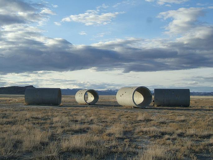 """Güneş Tünelleri, Nancy Holt, 1973-76. ABD'nin Utah Eyaleti'ndeki Lucin kasabası yakınlarında bulunan Great Basin Çölü'nde, gündönümü tarihlerine yakın zamanlarda, gün doğumu ve gün batımını Güneş Tünelleri içerisinden izleyebilirsiniz. Sanatçı Nancy Holt tarafından yapılmış anıtsal bir çalışma olan Güneş Tünelleri, her biri yaklaşık 5,48 metre uzunluğunda ve 2,74 metre çapında olan dört adet dökme beton boru kullanılarak inşa edilmiş. Tüneller, gündönümlerindeki gün doğumu ve gün batımlarını hizalayabilmek amacıyla büyük bir """"X"""" harfi biçiminde yerleştirilmiş. Boruların kenarlarında yer alan delikler, gündüz saatlerinde güneş ışığını iç duvarlarına yansıtarak Ejderha (Draco), Kahraman (Perseus), Güvercin (Columba) ve Oğlak (Capricorn) takımyıldızlarındaki başlıca yıldızların haritalarını meydana getiriyorlar. Güneş Tünelleri'nin yaratıcısı Nancy Holt, Robert Smithson'un eşi. Güneş Tünelleri, Arazi Kullanımı Yorum Merkezi tarafından ziyaret edilen yerlerden biridir. Fotoğraf:en.wikipedia.org/Calvin Chu from Riverside."""