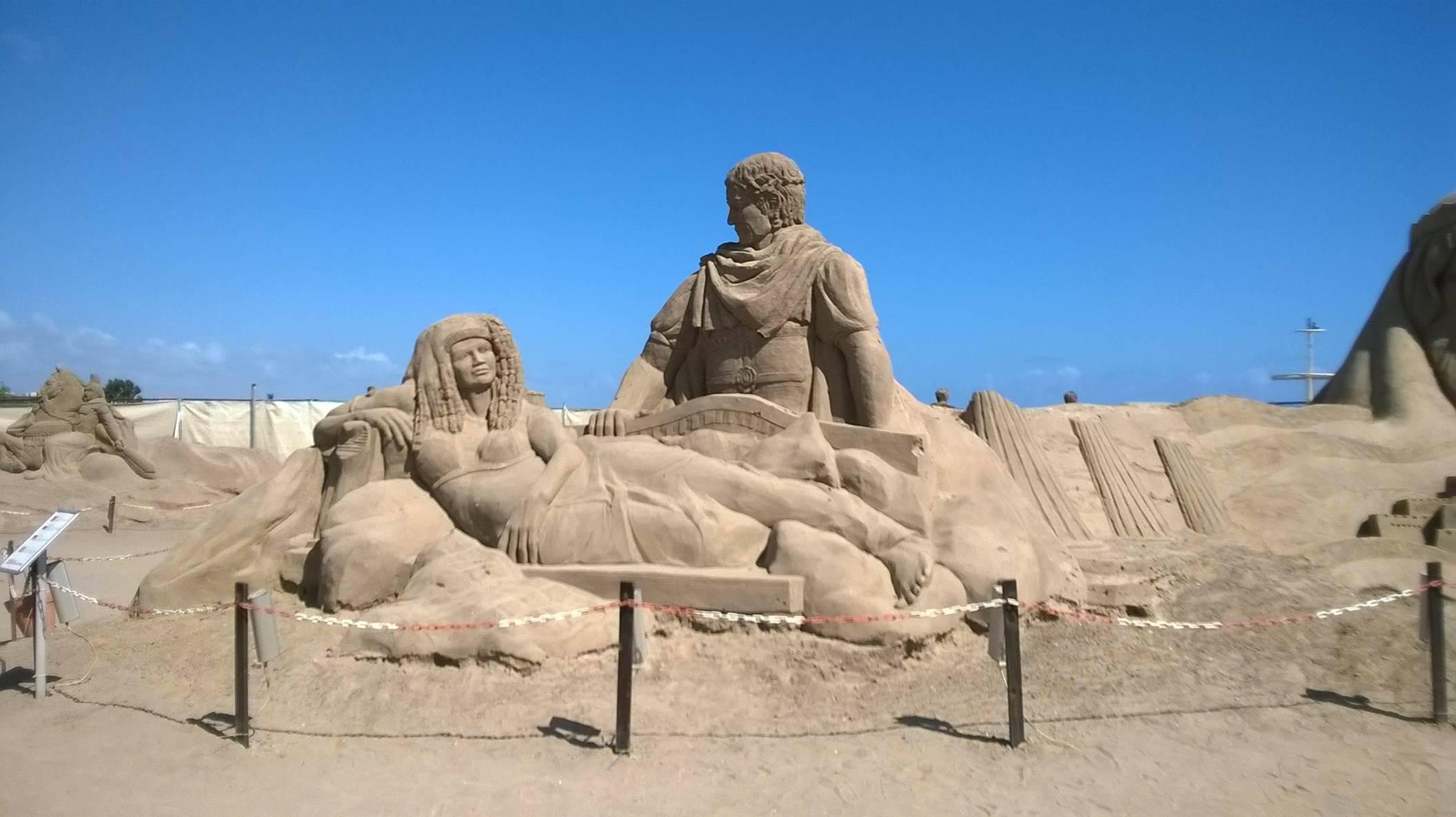 """Kum heykeller yalnızca kum ve su kullanılarak yapılıyor. Kum heykel sanatı son yıllarda dünyada yeni yeni yaygınlaşan özel bir """"ephemeral"""" (geçici) sanat türü. Kum organik ya da mineral olabilir. Organik kum tanecikleri, mercan, yumuşakçalar ve fosil parçacıkları barındırır. Tuzlu suda bunlara rastlanabilir. Mineral kum ya da kaya kumu ise mineral ya da kaya parçacıklarından oluşur. Heykelin sonunda aldığı şekli belirleyen, kullanılan kumun yapısıdır. Kum taneciklerinin boyutu ve yapısı bu bakımdan büyük önem taşır. Heykel için ideal tanecikler yuvarlak değil, karemsi olmalıdır. Plajlardaki kumlar çoğunlukla yuvarlak tanelidir; heykel yapımı için ideal diyebileceğimiz en uygun kum, nehirlerin yakınında bulunur ve dağlardan gelen su akıntılarıyla taşınır. Bu mineral kum tanecikleri köşelidirler ve birbirlerine uyarlar. M.Ö. 4000'lerde Mısır'da uygulandığı düşünülen bu sanat biçimi, günümüze kadar gelmiştir. 2006 yılından beri düzenlenmekte olan, bu yıl teması """"Dünyanın 7 Harikası ve Mitoloji"""" olarak belirlenen Uluslararası Antalya Kum Heykel Festivali, Antalya sahillerinde kum heykellere ev sahipliği yapıyor. Bu yıl 9 farklı ülkeden 22 heykeltıraşın katıldığı etkinlikte heykeltıraşlar 7.000 metrekarelik bir alanda 10.000 ton taşıma kum ile, 30 civarında tema ve yüzlerce devasa boyutta kum heykel canlandırıyor. Heykellerin büyüklüğü ve kapladıkları alan nedeni ile dünyanın en büyük kum olaylarından biri olan bu organizasyon Küresel Tasarım Sanat Çalışmaları tarafından organize edilmektedir. Fotoğrafta, Antalya Lara'da, İtalyan heykeltıraş Michela Ciappini tarafından canlandırılan Jul Sezar ve Kleopatra görülüyor. Fotoğraf: Feryal Tezcan"""