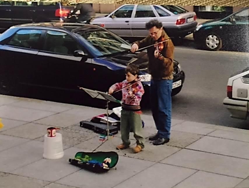 Berlin'de, Komischeoper'in önünde, gösteriyi izlemeye gelenlere müzik yapan bu –muhtemelen- baba-oğul, sizce Kamusal Sanat'ın alanına girer mi? Fotoğraf: Füsun Kavrakoğlu