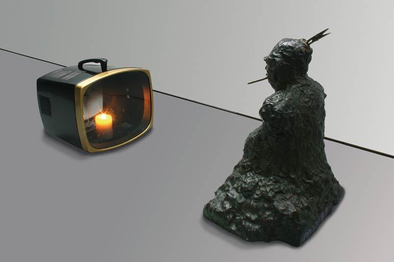 TV Buddha, Nam June Paik, 1976. Paik eserlerinde zaman zaman dinsel göndermeler de yapmıştır. Buda heykeli karşısında TV'de mum yanıyor. Buda, gerek zamansal, gerekse temsil ettiği değerler olan barış ve sükunet ile zıtlık oluşturan TV karşısına yerleştirilmiştir. Paik'in Buda'nın TV'de Buda'yı izlediği eserinde ise, 1970'lerin gösterişe düşkün ve kibirli dünyasına eleştiri vardır diyebileceğimiz gibi, dönemin iki önde gelen figürünü, Buda ile televizyonu, eski ve yeni dünyayı karşı karşıya getirmiştir; medyanın toplum üzerindeki etkisini vurgulamak istemiştir; Budist toplumların meditasyon yapmasına ironik bir yaklaşımdır da diyebiliriz. Buda TV'de kendini izleyerek meditasyon yapmakta, ama seyirci de bunu izlemektedir. Eserde, mahremiyet sorunu da gündeme gelmektedir. Paik'in eserlerinde izleyici için pek çok farklı yorum yapma imkanı vardır. Fotoğraf:lespeache.wordpress.com