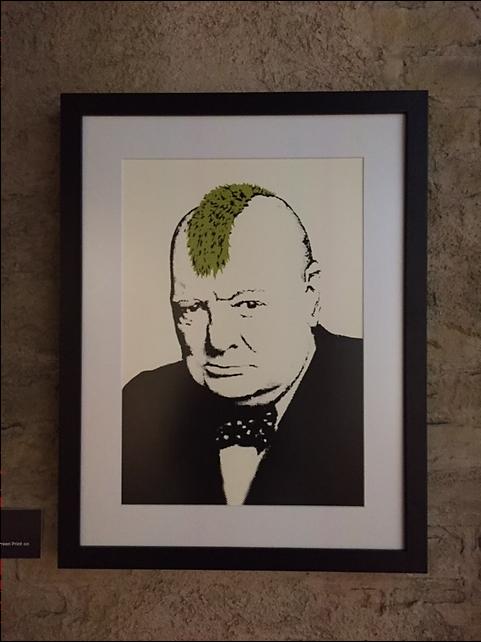 Turf War, 2003. Mohikan Churchill'den başka üzerine Warhol'un yüzünün boyandığı inek, polis renklerine boyanmış domuzlar, toplama kampı çizgilerine boyanmış koyunlar resmedilmiş Banksy eserleri de var. 2011 yılında Günah Kardinali adlı Liverpool'da bir galeriye verdiği çalışmada, Katolik rahipler tarafından istismar edilen çocuklar meselesini yansıtmak için, bir din adamına ait büstün yüzünü küçük banyo seramikleri ile mozaiklediği replikasını verdi. Mikelanj'ın Davut heykeline de intihar yeleği giydirmişti. Zeytin ağacından yapılmış, üzerine 284 asker ve bir terörist yerleştirilmiş Kudüs maketini Bristol Şehir Müzesi'ne hediye etti. Fotoğraf: Füsun Kavrakoğlu