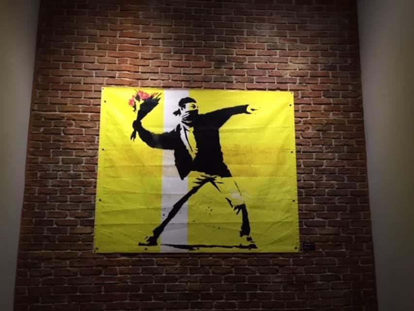 Flower Thrower, 2003. Londra'da bir müzik stüdyosunu kullanmaya başladığında ev sahibi ile kirayı grupların el ilanlarını yaparak ödemesi üzerinde anlaşmışlardı. Bu ilanların en unutulmazlarından biri, maskeli bir göstericinin öfkeyle Molotof kokteyli yerine bir demet çiçek atmak üzere olduğu çizimdi. Çiçek fırlatan maskeli gösterici çizimini (Riot Green) Bristol'de açılan sergiden 300 sterline alan öğrenci bu iş için öğrenim kredisini kullanmıştı. Daha sonra sanat piyasasından gelen ısrarlara dayanamayıp Sotheby's'de 78.000 sterline satmıştı. Çiçek Fırlatan Gösterici'nin 25. edisyonu için, Knightbridge'deki bir galerici, 70 bin pound istiyordu ve satış gerçekleşmişti. Fotoğraf: Füsun Kavrakoğlu