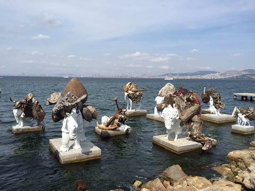The Most Beautiful of All Mothers (Tüm Annelerin En Güzeli), Adrian Villar Rojas, Troçki Evi, İstanbul Bienali, 2015. Tarih yapmış bir kişinin yakınlarıyla yaşadığı yıkık evi görüp, bakımsız bahçeden geçip kıyıya indiğimizde deniz kokusuyla birlikte Bienalin bize yaşattığı en unutulmaz anlardan birini yaşıyoruz. Adrian Villar Rojas'ın (1980-), Troçki'nin evinin kıyısına, çakıl plajın biraz açığında yarattığı heybetli heykel enstalasyonunda Troçki'ye doğrudan hiçbir gönderme yokmuş. Eser 20 kadar beton kaide üzerinde tek tek veya grup halinde duran 29 hayvan heykelinden oluşuyor. Hayvanların yüzü eve dönük. Beyaz fiberglastan yapılmış hayvanlar toprak renginde birer hayvanı sırtlarında taşıyor. Bu halleriyle hayali birer canavar oluşturuyorlar. Üstteki hayvanlar organik ve atık malzemelerle (deniz kabukları, balık ağları, kemikler, cam kırıkları, sebzeler, et) toprak, kum, tuz, asfalt, çimento, doğal pigmentler, kompost ve reçine karışımından yapılmış. Tuzlu suya dirençli olan alttaki hayvan ile onun sırtında duran ve deniz suyuyla aşınıp bozulmaya elverişli hayvan arasında bir tezat ve ittifak var. Bu hayvanlar belki de Troçki'nin korkularını, kabuslarını yansıtıyorlar? Fotoğraf: Füsun Kavrakoğlu