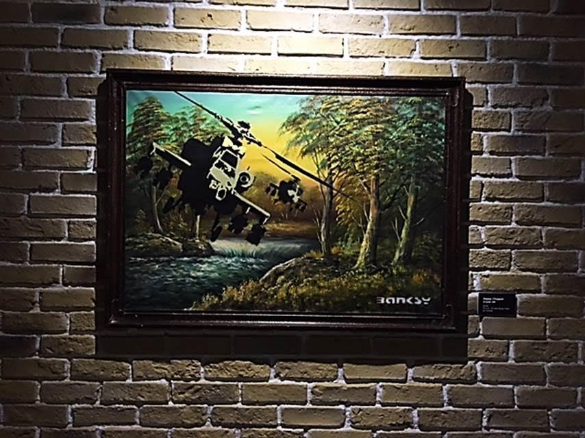 Happy Chopper Crude Oil, 2004. Mutlu Helikopter çalışması, çirkin görünümlü, ağır silahlarla donanmış helikopter başındaki kurdele ile daha tehditkar hale gelmiş. Peter Kennard, Constable'ın ünlü saman arabası tablosu üzerine 1980 yılında cruise füzeleri ilave etmişti. Çalışma, 2007 yılında Tate tarafından satın alınmıştı. Banksy, Millet'nin 1857 yılında yaptığı Başak Toplayan Kadınlar tablosunu da uyarlamıştı. Resimdeki kadınlardan biri çerçevenin kenarına oturmuş sigara içiyordu. Thomas Beach'in yaptığı, 18. yüzyıl aristokratına ait portreyi Banksy 2000 pounda satın almış ve üzerinde oynayarak aristokratı parmak hareketi yapar hale getirmişti. Tablonun adını Kaba Lord koydu. Fotoğraf: Füsun Kavrakoğlu, Global Karaköy, 2016.