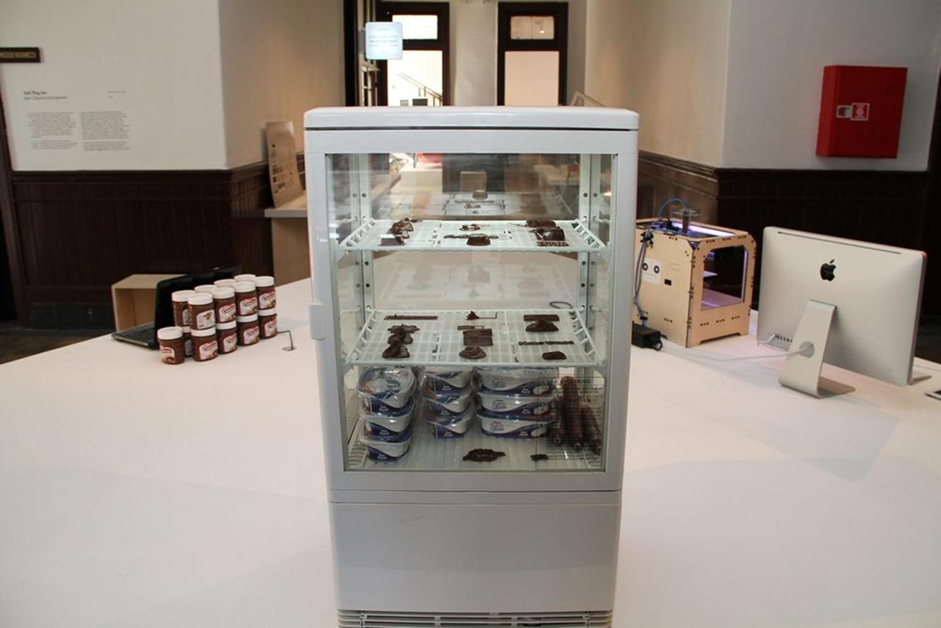 3. İstanbul Tasarım Bienali'nde yer alan Sokak Yiyeceği Yazıcısı projesi, Galata Rum İlköğretim Okulu, 2013. Sıradan plastik yerine çikolata ya da peynirle çalışmak üzere modifiye edilmiş üç boyutlu bir yazıcı olan Sokak Yiyeceği Yazıcısı, dijital ve analog malzemelerle yapılan deneysel bir çalışma niteliğinde. GG Lab'in projesi  üç boyutlu printerların yakın gelecekte mutfaklarımıza nasıl dahil olabileceğini ve yepyeni deneysel yiyeceklerin üretiminde kullanılabileceğini kanıtlıyor. Bu projeyle üretim teknolojisi, mimarlık ve avangard mutfak arasında ortak bir buluşma noktası oluşturuluyor. Sokak Yiyeceği Yazıcısı, halkı yemek tasarımlarıyla buluştururken, aynı zamanda dijital ve analog malzemelerle yapılan deneysel bir çalışma niteliğine de sahip. Aynı sergide yer alan, doğaçlamayı seri üretime katmak için tasarlanan bir döner kalıp makinası olan ve Annika Frye tarafından geliştirilen Improvisation Machine/Doğaçlama Makinesi ise seramik objelerin sabit bir kalıp olmadan, polimer bir harç kullanarak yapılmasını sağlıyor ve üretime müthiş bir özgürlük kazandırıyor. Fotoğraf:http://www.poetikhars.com/webblog/sepp/adhokrasi