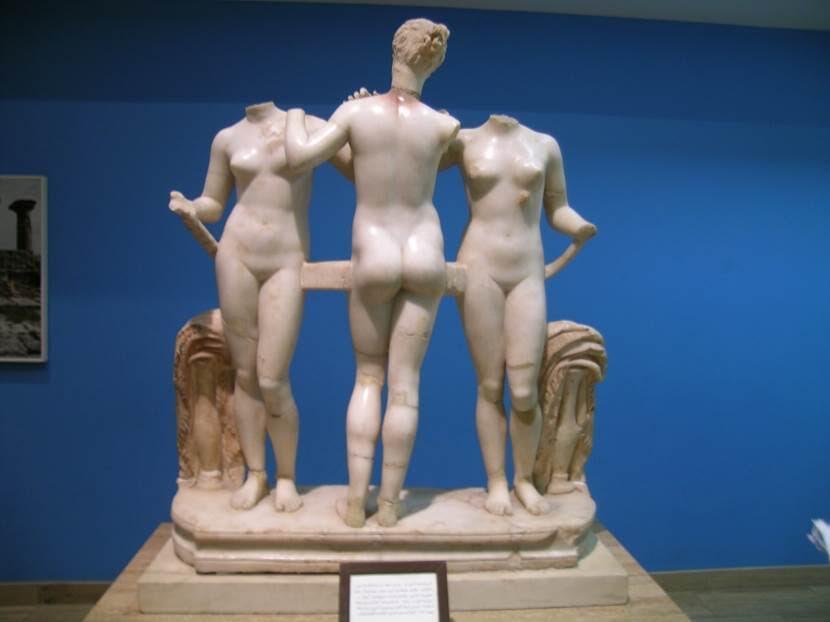 """Cyrene'deki Roma Hamamı'nın soğukluk bölümünden Üç Güzeller. Efsaneye göre yeryüzündeki ilk güzellik yarışması Yunan Tanrıçaları Hera, Aphrodite ve Athena arasında yapılmıştır. Kral Peleus ile deniz perisi Thetis'in düğününe çağrılmayan Fesatlık Tanrıçası Eris, düğüne davetsiz olarak gidip ortaya üzerinde """"en güzele"""" yazan bir altın elma atar. Zeus en güzeli seçmesi ve elmayı ona vermesi için Troya Kralı Priamos'un oğlu Paris'i (o sırada çobandır) görevlendirir. Paris de, kendisine dünyanın en güzel kadınının yani Sparta Kralı Menelaos'un karısı Helena'nın aşkını sunan Aphrodite'i seçer. Tarih boyunca bu üçlüyü işleyen pek çok eser yapılmıştır. Libya'da Cemahiriye Müzesi'nden başka Sabratha'nın tiyatrosunda da Üç Güzeller'i gördük. Fotoğraf: Füsun Kavrakoğlu"""