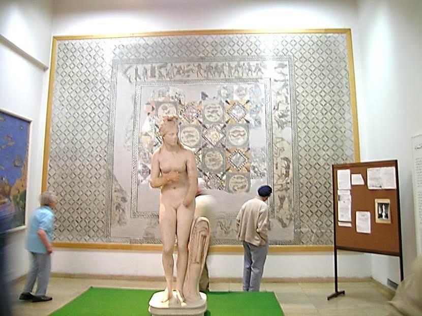 Cyrene Venüsü. Bir ara Göring'de kalmış, 1999 yılında Libya'ya geri verilmiş. Arkasında, MS 2. yüzyıla tarihlenen, bir Roma villasına ait mozaik tablo. Fotoğraf: Füsun Kavrakoğlu