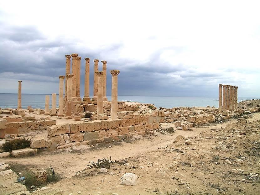 Sabratha'daki İsis Tapınağı. 1. yüzyıla ait, Mısır'ın en büyük tanrıçası İsis adına yapılan tapınağın yüzü denize dönük. Mısır'da Annelik ve Bereket Tanrıçası olan İsis, Sabratha'da denizcilerin tanrısı olarak kabul görmüş. Etrafı sekiz sıra korint sütunu ile çevrili olan İsis Tapınağı'nda ilkbaharda denizcilik mevsiminin başlangıcını kutlamak için festival yapılırmış. Sabratha'da ayrıca Serapis, Antonine adına yapılmış tapınaklar da var. Kartacalılar ve daha sonra da Romalılar zamanında çalışmış olan Kuzey Afrika mermer ocaklarının bazılarının  ocak yolları İkinci Dünya Savaşı sırasında atılan bombalarla bozulmuş ve faaliyetleri durmuştur. Gezdiğimiz tapınaklarda genellikle beyaz, yeşil dalgalı dairevi bantları olan Cipoline mermeri kullanılmıştı. Fotoğraf: Füsun Kavrakoğlu