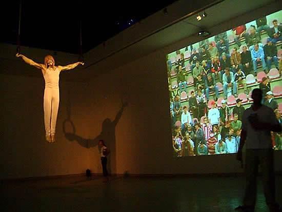 Venedik Bienali 2003'te Çek Cumhuriyeti ve Slovak Cumhuriyeti ortak pavyonuna giren kişiler dijital bir numeratör ile sayılıyor. Jimnastik kıyafeti içindeki Hazreti İsa halkada. Duruşu bize çarmıhtaki duruşunu hatırlatıyor. Tavan siyah ve mavi yıldızlarla kaplı. İsa'nın her iki yanındaki duvara bir stadyumda oturan kişiler yansıtılmış. Birkaç dakikada bir İsa'nın üzerinde sarı flaş patlıyor, o sırada filmdeki izleyiciler tezahürat yapıyor. Bu, Çek Cumhuriyeti'nden Kamera Skura adlı grup ile Slovakya'dan Kunst-Fu adlı grubun ortak eseri. Çek ekip kendi işlerini gayri-ciddi ve absürt olarak tanımlarken, daha çok performans sanatı ile ilgili projeler gerçekleştirdiklerini;  Slovak ekip ise, ironi ve paradoksun onlar için anahtar kelimeler olduğunu, daha çok video işleri yaptıklarını belirtiyorlar. Bu ortak proje, dini bir idol ile ruhsal hareketi, spor ile de bedensel hareketi ifade ederek, ruhsal ve bedensel dünyanın toplamı olan insanı ifade ediyormuş. Fotoğraf: Füsun Kavrakoğlu