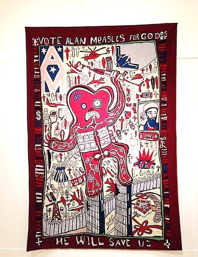 Tanrı Olarak Alan Measles'a Oy Verin, Grayson Perry, 2007. 2015 yılında Pera Müzesi'nde sergilenen el yapımı yün halı. Perry bu halıyı çok beğendiği Afgan savaş halılarını temel alarak tasarlamış. Tanrı için oy verme fikri kışkırtıcı gibi görünse de sanatçı bununla daha çok konuşmayı ve bir tartışma başlatmayı hedeflemiş olduğunu belirtiyor. Perry, Londra Metrosu'nun bombalanması, İkiz Kuleler'e saldırı, İsrail'in Batı Şeria'daki duvarı ve Usame bin Ladin göndermeleri ile teröre karşı savaşın birçok yüzünü esere katmak istemiş. Sanatçının niyeti izleyicinin Birleşik Krallık'ta politik özgürlüğün ne derece kanıksandığını ve yerkürenin her yerinde insanların seslerini duyurmak ve adil biçimde temsil edilmek için mücadele ettikleri gerçeğini test etmektir. Eserlerinde yün, pamuklu, ipek halı; akrilik, sırlı seramik, polyester ve yedirme baskı yöntemini kullanan Grayson Perry'nin üç ana teması sınıf ve tüketicilik; din ve inançla ilgili fikirler ve kimliktir. Fotoğraf: Füsun Kavrakoğlu