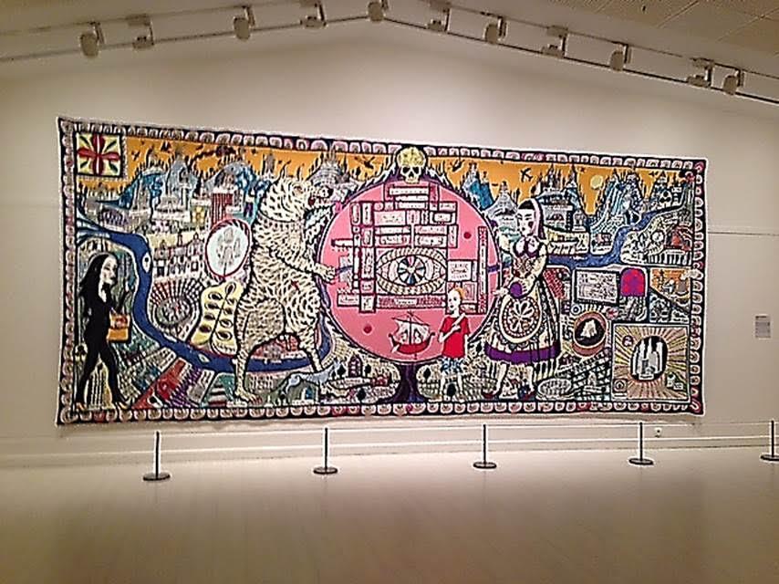 Gerçekler ve İnançların Haritası, Grayson Perry, 2011. Gerçekler ve İnançların Haritası adlı eser, her köşesinde ayrı bir konu bulunan bir halı. Hac fikrinden etkilenen sanatçı, hac mekanı olarak gördüğü her sembolü, yeri, yapıtı, düşünceyi bir halı üzerinde toplamış. Halının ortasında solda betimlenen ayı, hayatın doğal ve vahşi yanını; sol alt köşedeki modern giysili kadın, tüketim dünyasını; ortadaki küçük çocuk, masumiyeti; orta bölümdeki etnik giysili kadın ise geleneği temsil ediyor. Bu harita yolumuzu bulmamız için değil, ne denli kayıp olduğumuzu fark etmemiz için yapılmış gibi duruyor. Pera Müzesi, 2015. Fotoğraf: Füsun Kavrakoğlu