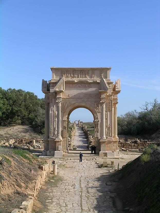 Ören yerine 203 yılında yapılan, imparatoru ailesi ile birlikte gösteren görkemli Septimus Severus Kemeri'nden giriliyor. Roma şehri kurulurken kuzey-güney doğrultusunda bir ana cadde (cardo maximus), doğu-batı doğrultusunda bir ana cadde (decumanus maximus) tasarlanırdı. İki ana caddenin kesiştiği nokta, kolonlu anıtsal bir kavşak noktası ile süslenirdi. Roma'da caddeler birbirini dik keserdi. Caddenin mutlaka düz olması istenirdi. Caddenin düz olmaması yüz kızartıcı bir sebepti. Via recta, düz cadde, Roma mühendisliğinin yüz akı idi. Fotoğraf: Füsun Kavrakoğlu