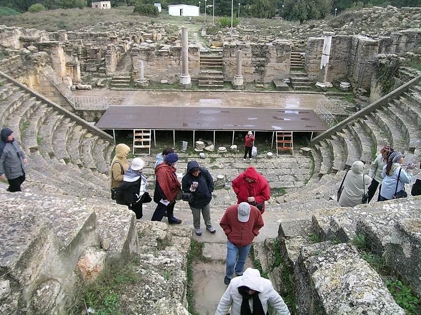 Cyrene'nin tiyatrosu. Kentin en zengin dönemi olan MÖ 4. yüzyılda Artemis Tapınağı yapıldı ve nekropol kuruldu. MÖ 331 yılında Cyrene Büyük İskender'in idaresine geçti. Sonra gelen Ptolemy Hanedanı döneminde kente tiyatro ve gimnasyum yapıldı, kentin her yanı çeşmelerle süslendi ve kent, 5,5 km uzunluğunda bir sur ile çevrildi. Kentin en eski yapılarından biri olan tiyatronun Yunanlar tarafından yapıldığı düşünülüyor. Buradaki en eski kalıntılar, sahne ve orkestraya çok yakın oturma yerleri Yunanları işaret ediyor. Tiyatro bin kişi alabiliyor. Burası Romalılar tarafından amfitiyatroya dönüştürülmüş. Amfitiyatro, gladyatör ve vahşi hayvan oyunları için kullanılan, daire ya da elips biçimli, yükselen tribünlerden oluşan bir yapıdır. Tiyatro, yarım daire bir yapı iken, amfitiyatro çift tiyatro, yani dairesel ya da elips şeklindedir. Amfitiyatrolar ahşap malzeme yerine taşla yapılırdı. Cyrene'de de vahşi hayvan oyunları için yapıyı kullanabilmek için, ilave oturma yerleri eklenmiş, sahneye çok yakın olan oturma yerlerinin bulunduğu yere bir duvar yapılmış, sahneye giriş çıkış için bir tünel inşa edilmiş. Cyrene'de bir tiyatro daha olduğu ama 262 yılındaki büyük depremde yıkıldığı düşünülüyor. Fotoğraf: Füsun Kavrakoğlu