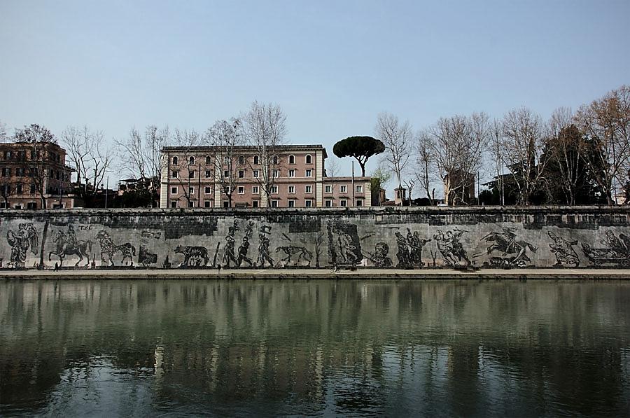 Zaferler ve Ağıtlar: Roma İçin Bir Proje, William Kentridge, 2016. Roma'da, Tiber Nehri kıyısında Güney Afrikalı sanatçı William Kentridge'in (1955-) Mazzini ve Sisto Köprüleri arasında yer alan, 550 m boyunca uzanan duvar resmi, Roma'nın 2769 uncu kuruluş yıldönümünü kutlamak için tasarlandı. Bu alan, Roma'da Çağdaş Sanat'a tahsis edilen ilk ve en büyük yer olduğu gibi, Avrupa'daki en büyük açık hava sergisi. Sanatçı, nehrin kıyısındaki duvarlarda biriken kir ve yosun tabakasını, hazırlanan şablonların duvarlara yerleştirilmesi ve şablonların içinin ya da etrafının temizlenmesi yöntemiyle şehri simgeleyen figürler oluşturdu. Kentridge kullandığı tekniğin Banksy'ninkinin tam tersi olduğunu, boyama değil temizleme yöntemiyle çalıştığını söylüyor. Sanatçı, şehrin havasının, suyunun bıraktığı lekelerden oluştuğu için eserinin, Roma'nın doğal bir parçası olduğunu; 3-4 yıl içinde, doğal bir süreçle yok olacağını belirtiyor. Eserin zaman içinde yok olmasının da projenin bir parçası olduğunu; eserinin de dünyadaki her şey gibi dönüştüğünü ve geçici bir karakter taşıdığını söylüyor. Kentridge'in halı tasarımları, baskıları, operalar için sahne tasarımı, heykelleri ve animasyon filmleri de var. Filmleri 2004 Cannes Film Festivali'nde gösterilmiş. Kendisi çok yönlü ve başarılı bulunan bir sanatçı. Fotoğraf:www.purple-home.com