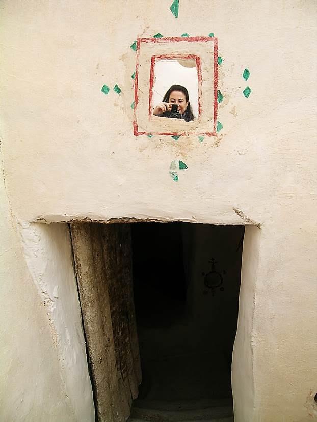 Kadın, evine girip çıkarken aynaya bakıyor. Fotoğraf: Füsun Kavrakoğlu