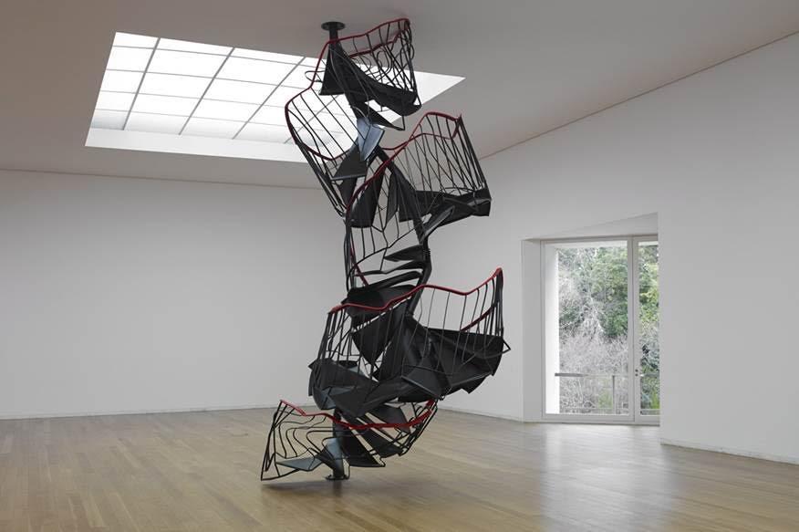 Merdiven, Monika Sosnowska, 2010. Polonyalı sanatçı, mimari ile heykeli, mekanın şiirselliğini ve siyasasını deneyimlemek için, birleştiriyor. Monika Sosnowska (1972-), eserlerini kıvırarak, bükerek, sıkıştırarak, çökerterek mekana yerleştiriyor; yanılsamaya neden olan işler üreterek mekanın ve yapının algılanışını değiştirmeyi amaçlıyor. Polonya halkının yaşadığı hayal kırıklığının sanatçıyı etkilemeye devam ettiği düşünülüyor. Varsayılan şeylere güvenilemeyeceği Sosnowska'yı etkileyen fikirlerden. Eser, 2010 yılında İsrail'de, 2012'de Polonya'da, 2012-13'te Shanghai Bienali'nde, 2014 yılında Berlin'de, her seferinde mekana uyarlanarak, sergilenmiş. Merdivenin  işlevselliğini kaybetmiş olması ile totaliter rejimlerin çöküşü arasında bir paralellik düşünülüyor. Babil Kulesi de eserin düşündürdüklerinden. Tamamlanamamış anıt,  söylemin ve yapıtın negatif anlamda eksikliğine, sürekli eksik kalışına değil, pozitif anlamda söylemin ve yapıtın sonsuz-yeniden-yapımına, dolayısıyla var ol(a)mayanı var etme, görünür ol(a)mayanı görünür kılma, yüzü ol(a)mayana yüz verme, sesi ve dili ol(a)mayanları konuşmaya katma arzusuna işaret eder. Yapısöküm mimarisinde  mekan olgusuna sabit ve değişmez bir nesnellik olarak değil, sürekli devinen bir hareket olarak  bakmak söz konusudur. Derrida Babil Kulesi'nin dillerin çeşitlenmesine indirgenemeyeceğini; Babil Kulesi'nin kendini her zaman başkalaşıma ve ötekiliğe açan, hiçbir zaman inşası bitmeyen, hiçbir zaman tam anlamıyla anıt olamayan bir yapıdır ve yapının tamamlanamıyor olması felsefenin temel yapısını oluşturur. Derrida'ya göre hiçbir söylem, metin ya da yapıt tamamlanmamıştır; her metin, kendi içinden yeni bir metnin doğmasına olanak tanır ve bu sayede kendini yaşatır. Fotoğraf:polishartandtea.tumblr.com