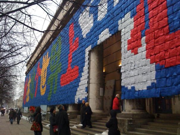 """Ai Weiwei, Haus der Kunst, Münih, 2009. Üzgünüm adlı retrospektifinde binanın cephesine yaptığı Hatırlama adlı duvar resmi. Bu eserde 9000 çocuk sırt çantası kullanılarak, """"Bu dünyada mutlu bir şekilde yedi yıl yaşadı"""" yazılmıştı. 2008 yılındaki Sichuan depreminde çocuklarını kaybeden annelerden birinin sözüydü bu. Derme çatma yapılmış okul binaları çökünce binlerce çocuk hayatını kaybetmişti. Mayıs 2008'de Richter ölçeğine göre 8 büyüklüğündeki depremde 70.000 kişi ölmüştü. Ölenler arasında okul çocuklarının oranı çok yüksekti. Komşu binalar ayakta kalırken çok sayıda okul yıkılmıştı. Çin'in tek çocuk politikası yüzünden ölenlerin çoğu ailenin tek evladıydı. Ai Weiwei okul binalarının çökme nedenlerinin araştırılmasına katılmıştı. Fotoğraf:www.hydramag.com"""