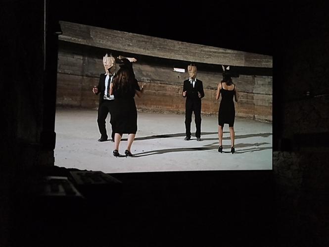2084: bir bilimkurgu gösterisi/2. Bölüm: Cumhuriyeti'nin Çöküşü; Pelin Tan (1974-), Anton Vidokle (1965-); video, ses; 2014. Sanatçıların yönetimi altındaki bir cumhuriyet ve devamında, yaşamı durmaksızın sanata dönüştürme gayreti yüzünden bu cumhuriyetin çöküşü.  Bu cumhuriyette müzeler veri merkezleridir, hiç kimsenin bir mesleği yoktur, para kaldırılmıştır, artık iş de yoktur. 14. İstanbul Bienali, Adahan Sarnıcı, 2015. Fotoğraf: Füsun Kavrakoğlu